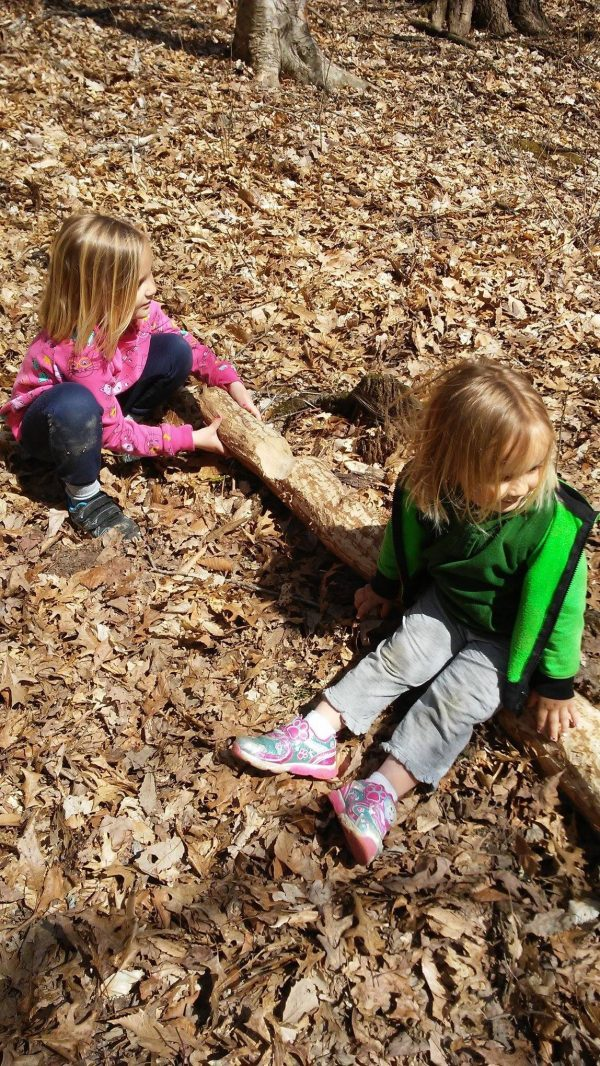 young children sitting on leaves - homesteading