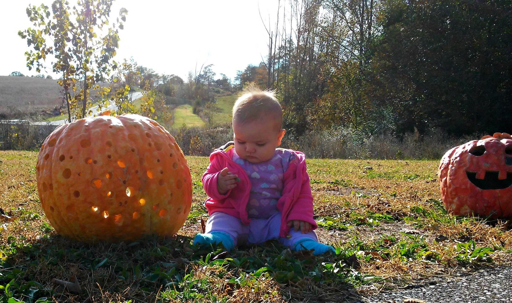 baby sitting next to a pumpkin