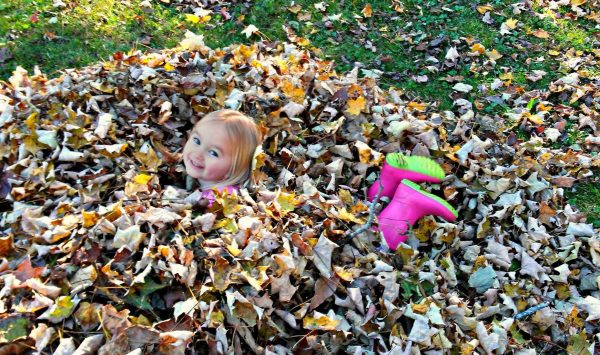 young girl playin in leaves - homesteading